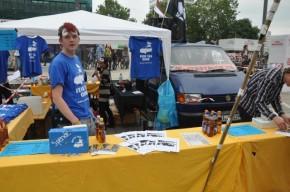 Der Stand der Jungen Gemeinde Jena bei der Demonstration Freiheit statt Angst. Im Vordergrund sieht man einen Verkaufstisch mit einem gelben Tuch. Auf diesem Tisch sind Flaschen mit Soli-Mate, eine Spendenbox und Informationsmaterial. Im Bildhintergrund ist ein weißes Partyzelt an dem das Soli-T-Shirt hängt.